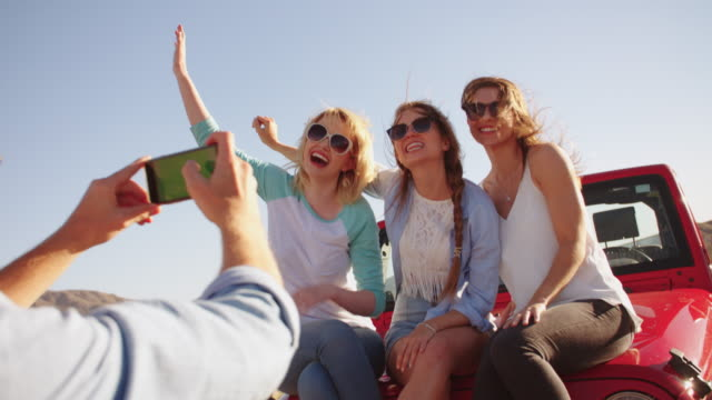 Man Taking Photo Of Three Women On Road Trip Shot On R3D video