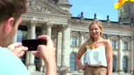 Man taking photo of woman video
