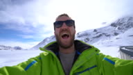 Man taking selfie in winter by frozen mountain lake video