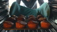 Man Taking Tray Of Baked Muffins Out Of The Oven video