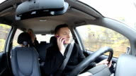 Man talk on mobile phone and drive car at the same time video