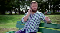 Man talking by smartphone, on bench in park. Steadicam. video