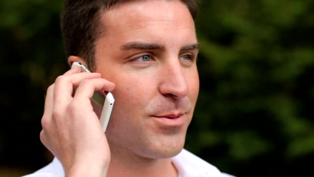 Man talking on cell phone outdoors video