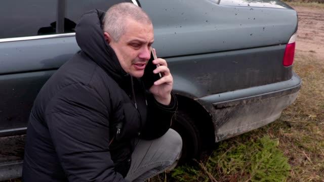 Man talking on phone near stuck car in the mud video