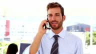 Man talking on phone while colleague works behind him video