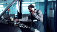 Man talking phone and doing engine diagnostic video