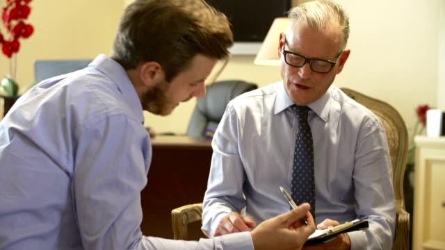 Man Talking To Financial Advisor In Office video