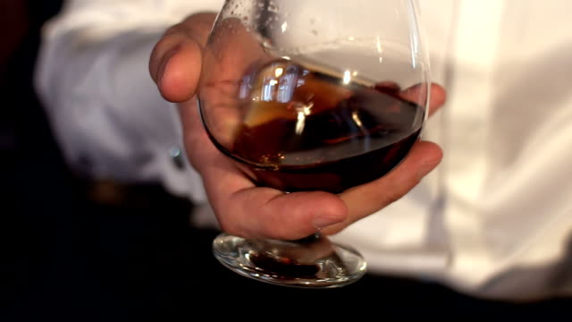 Man tasting a glass of cognac, slow motion. video
