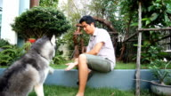 Man teaching his dog in hold hands video