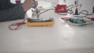Man Testing circuit board in his office. video