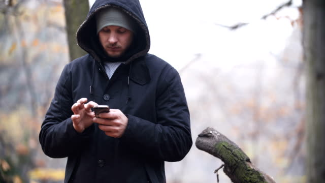 Man Texting on Bench in Autumn Park. video