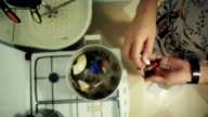 Man throw details from music equipment in boiling saucepan with inedible objects video