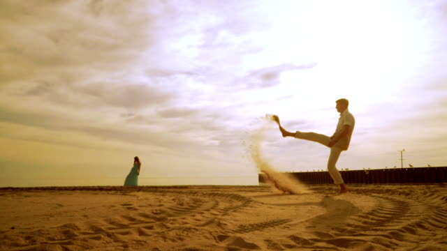 Man throwing sand with foot. Happy man having fun on beach. Woman stand on beach video