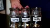 A man throws a coin in a piggy bank. On jars glued white stripes. video