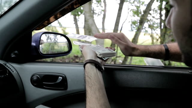man throws money out the window of a car video