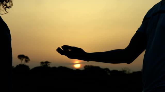 Man touching beloved woman's hand. Romantic proposal at sunset. Magic video