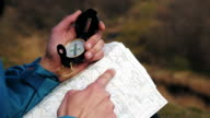 Man tourist in a blue jacket looking on the compass and map video