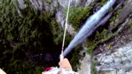 Man traverses highline stretched above waterfall, valley video