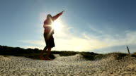 Man traverses slackline stretched above sandy dune area video