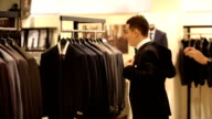 man tries on the suit in the store video