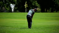 Man tries to get ball in hole at the course video