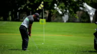 Man tries to get the ball in hole at golf field video