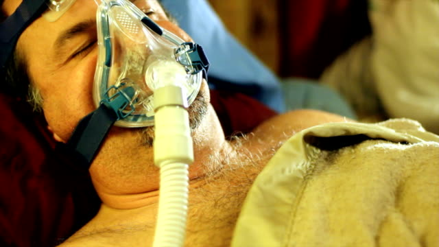 man tring to sleep with a cpap mask video