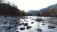 Man trowing rocks by the river video