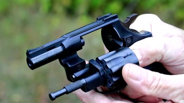 Man turns cylinder of black revolver video
