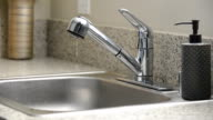Man turns off dripping kitchen sink faucet video