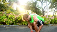 Man tying his shoe laces while jogging in park video