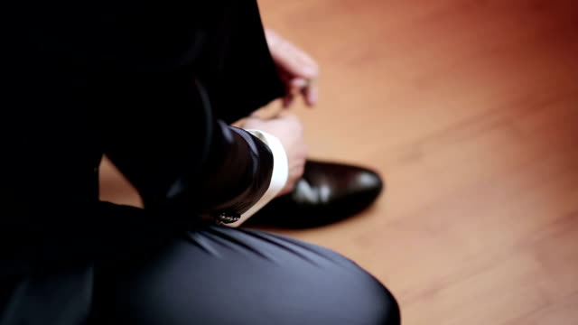 Man tying patent leather shoes video