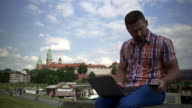 Man typing on a laptop and answering smartphone. video