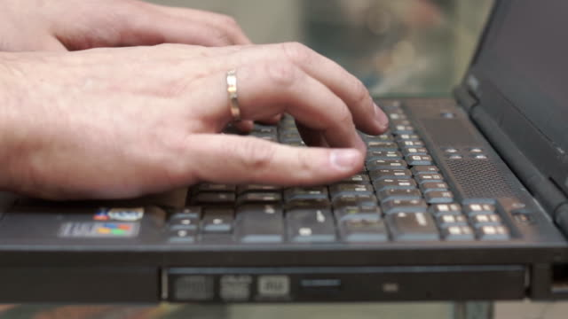 man typing on old, ancient laptop video