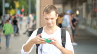 Man typing on phone in the middle of a street. Young guy texting on smartphone. video
