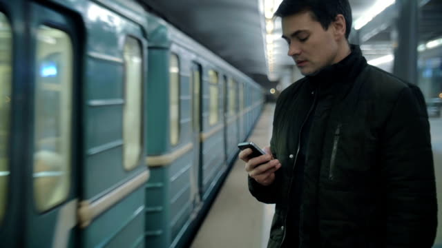 Man typing sms standing on the subway platform video