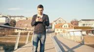 MS TS Man Typing SMS While Walking On Bridge video