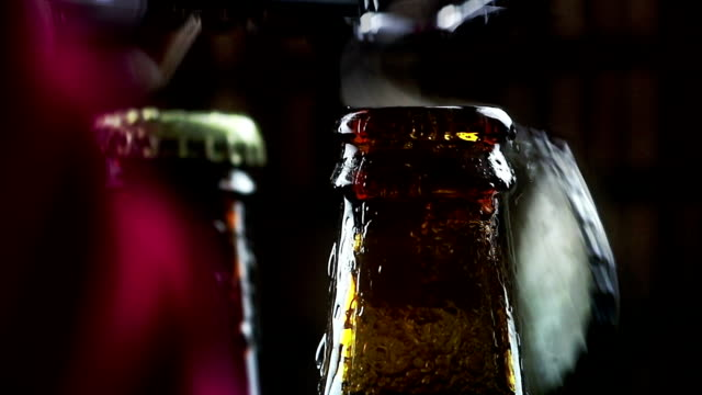 man uncap three bottles of fresh beer with foam and drops on dark background pub video