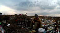 man unemployed homeless dirty looking food waste dump in landfill  social video video