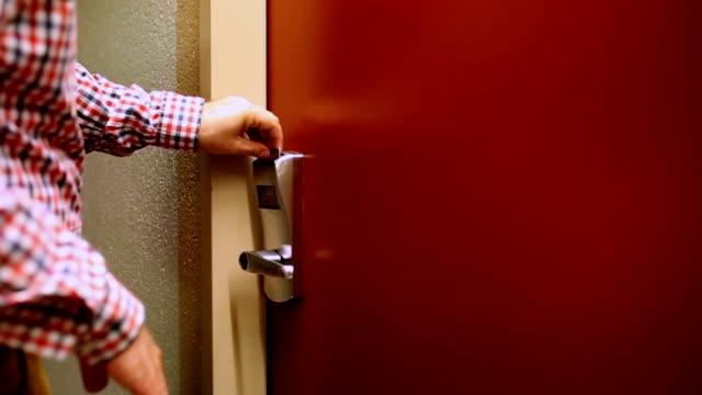 Man unlocks the door of the hotel room card video