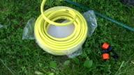 Man unwinding yellow watering hose video