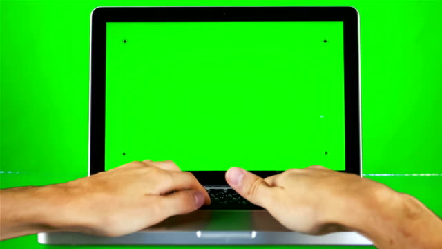 A man use a laptop on his desk. Green screen . video
