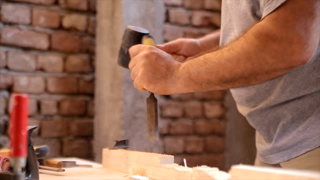 A man uses a chisel in his workshop video