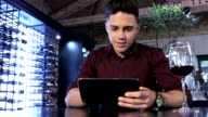 Man uses a tablet at the restaurant video