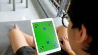 A man uses a tablet PC at sofa, Chroma key screen video