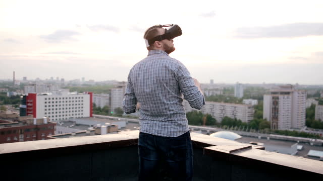man uses a virtual reality glasses on the roof video