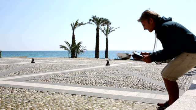Man uses digital tablet at beach video