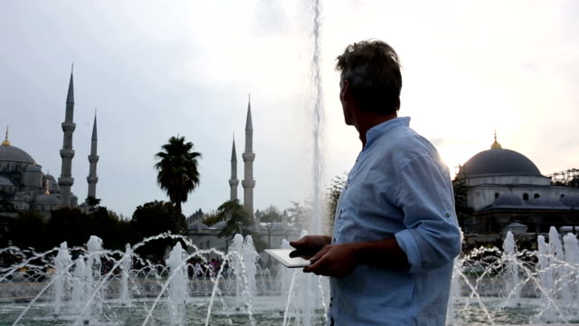 Man uses digital tablet, in front of Blue Mosque, Istanbul, Turkey video