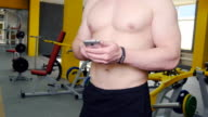 man uses fitness tracker in the gym video