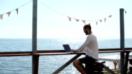 man uses laptop on background of sea video